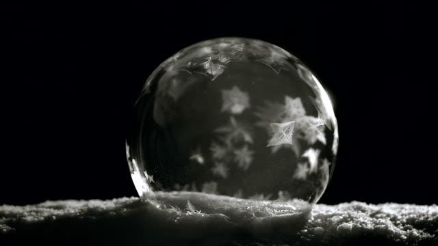 kristal buz topu yavaş yavaş siyah arka plan üzerine dondurma - donmuş su stok videoları ve detay görüntü çekimi