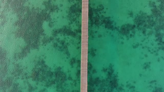 Crystal-clear Turquoise Ocean with Long Wooden Jetty at Sunrise, Aerial Top View
