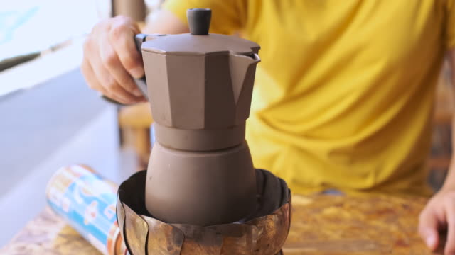 cu slow motion coffee in moka pot on gas stove on table in cafe.handmade coffee.