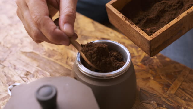 cu slow motiopn hand put fresh ground morning coffee powder in to coffee tablet of moka pot. - grindare video stock e b–roll