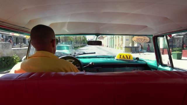 Cuban chauffeur driving 1950's american vintage classic car through old Havana, Cuba