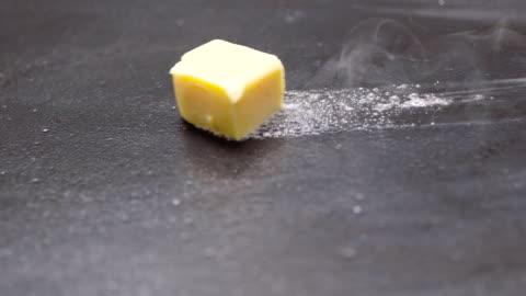 vidéos et rushes de cube de beurre fondre grésillant browning dans poêle poêle anti-adhésives en slow motion, préparation pour la cuisson - fps 50 - panoramique