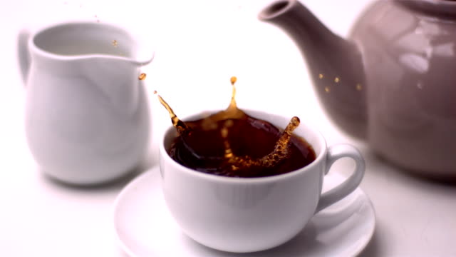cube of sugar falling in tea cup - tea cup stock videos & royalty-free footage