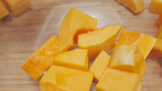 Cubes of Butternut Squash Dropping into a Glass Serving Bowl in 4k video