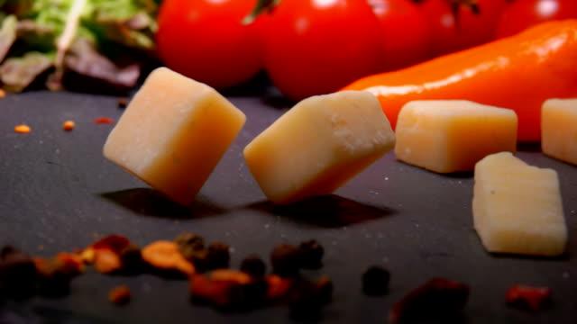 パルメザン チーズのキューブがテーブルの表面に落ちる - 田舎のライフスタイル点の映像素材/bロール