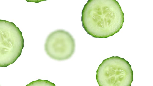 Cucumber slices falling down on white background with alpha mask 4K UHD footage