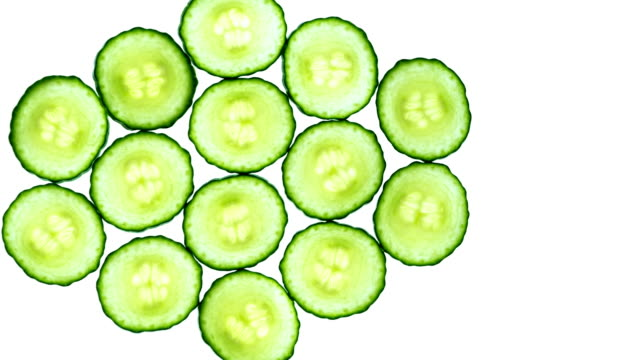 Cucumber slices on white background. video
