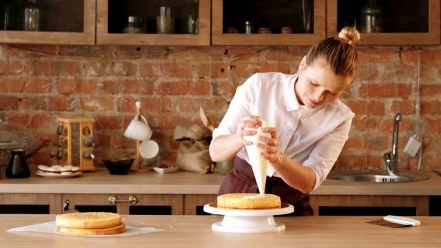 vidéos et rushes de chef pâtissier de classe de maître culinaire assemblant le gâteau - boulanger