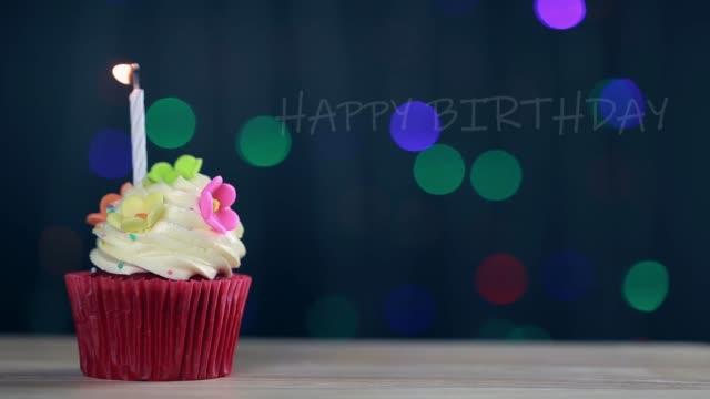 tasse kuchen und alles gute zum geburtstag text auf dem bildschirm hintergrund. geburtstag cupcake mit einer einzigen blauen kerze. - geburtstagstorte stock-videos und b-roll-filmmaterial