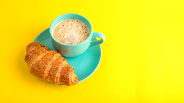 Une tasse de café et un croissant. Fond jaune clair. manger le petit déjeuner. mordre de cuisson dessert. Séquences vidéo stop motion timelapse. Café take away (aller) - Vidéo