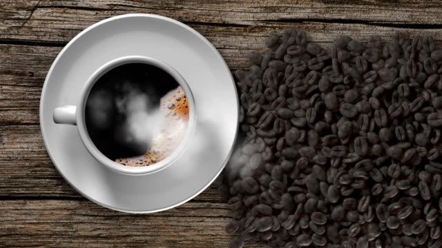 一杯のコーヒーと古い木製テーブルの上のコーヒー豆。 - 木目点の映像素材/bロール