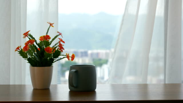 Cup of coffee and flower on the table by the curtain