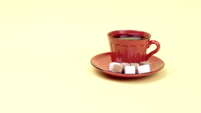 a cup of coffee and sugar cubes on a yellow background. - piattino video stock e b–roll