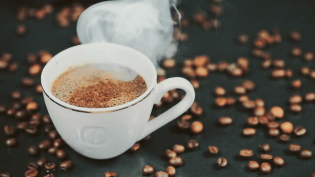 A Cup of Coffee. Falling grains of coffee on the table. Slow motion video