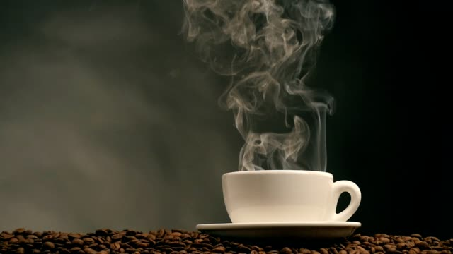Cup of coffee on dark background. Slow motion video