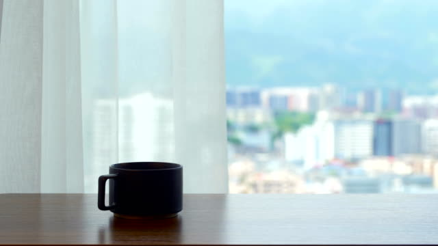 Cup of coffee on the table by the curtain