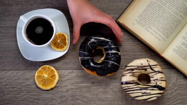 stockvideo's en b-roll-footage met kopje koffie met boek over houten tafel - literatuur