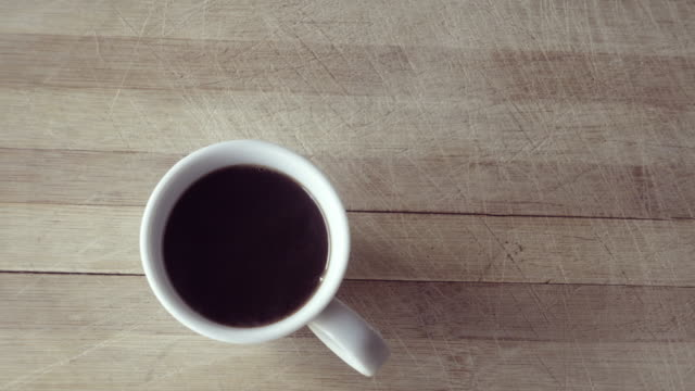 A cup of coffee with hot coffee on a kitchen table video