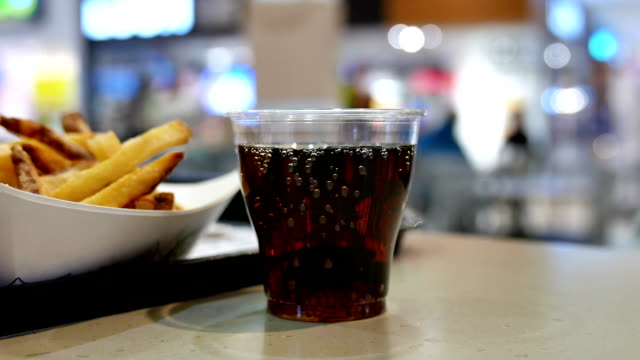 A cup of cola and fries on table at food court video