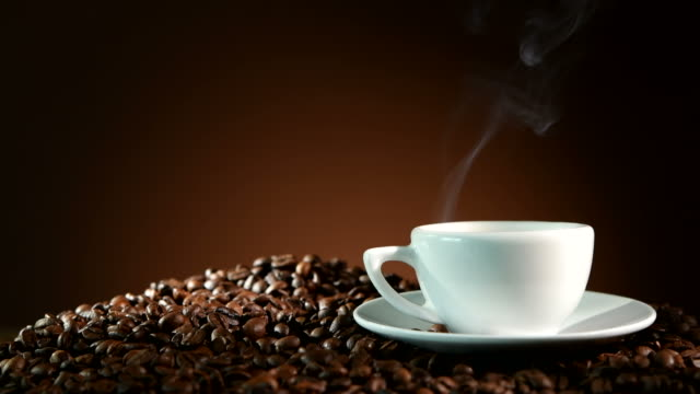 Cup of espresso with coffee beans and steam