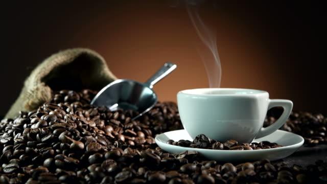 tasse espresso mit kaffeebohnen, beutel, schaufel und dampf - kaffeetasse stock-videos und b-roll-filmmaterial