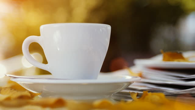 A cup of fresh hot drink on table with falling autumn leaves, outdoors in autumn