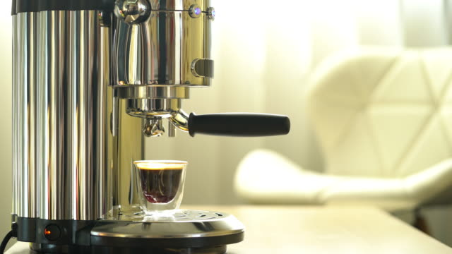 Cup of freshly made coffee and espresso maker in a sunlit room, office or home