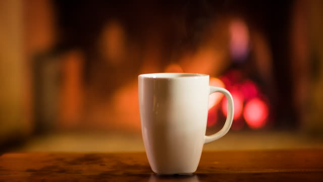 Cup of hot beverage in front of a fireplace Cup of hot beverage in front of a flaming fireplace in a cozy wooden cabin. mug stock videos & royalty-free footage