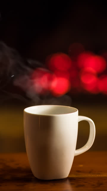cup of hot beverage in front of a fireplace - vertical format video stock videos and b-roll footage