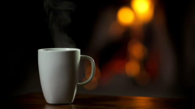 Cup of hot beverage in front of fireplace video