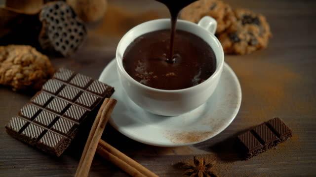 vídeos de stock, filmes e b-roll de xícara de chocolate quente, paus de canela e chocolate na mesa de madeira - chocolate quente