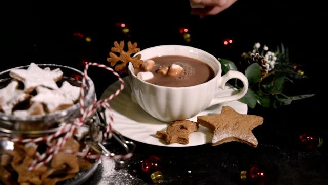 vídeos de stock, filmes e b-roll de um copo da bebida quente do cacau com bolinhos em forma de estrela caseiros do pão de gengibre - chocolate quente