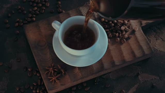 Cup of hot coffee with roasted beans on rustic wooden background - vídeo