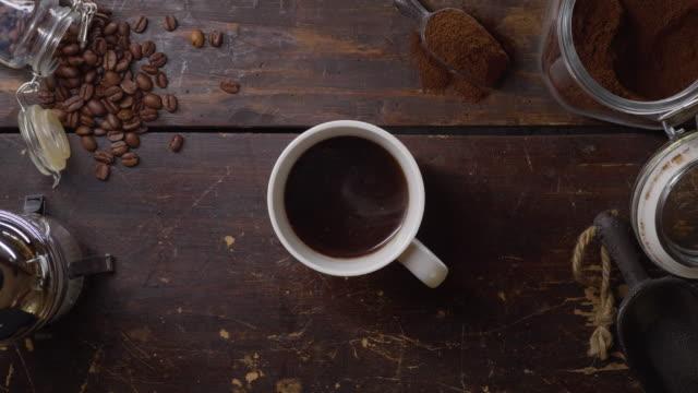 eine tasse heißen frischen kaffee auf einem holztisch - kaffeetasse stock-videos und b-roll-filmmaterial
