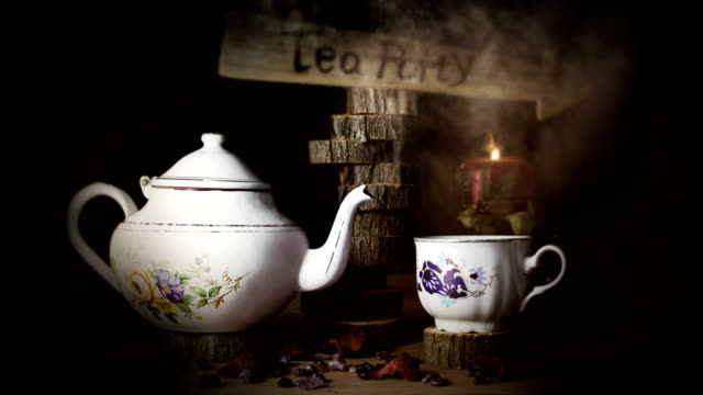 cup of tea and teapot on wooden table with arrow sign, smoke ,candle flame and light in the background. tea party concept - teapot stock videos & royalty-free footage