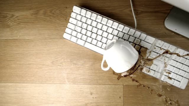 Cup of tea spilled out over a white keyboard video