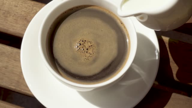cup on a saucer on a wooden table in the morning - lattaio video stock e b–roll