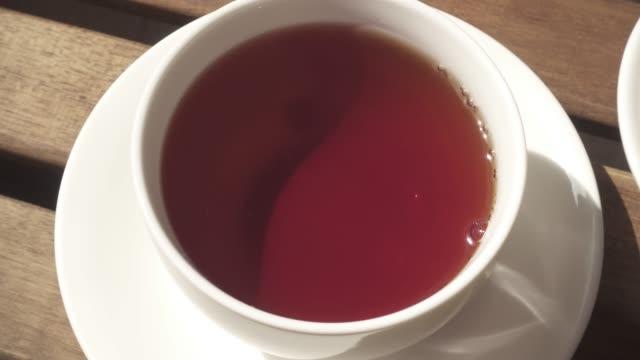 朝の木製テーブルでソーサーにカップ - ソーサー点の映像素材/bロール