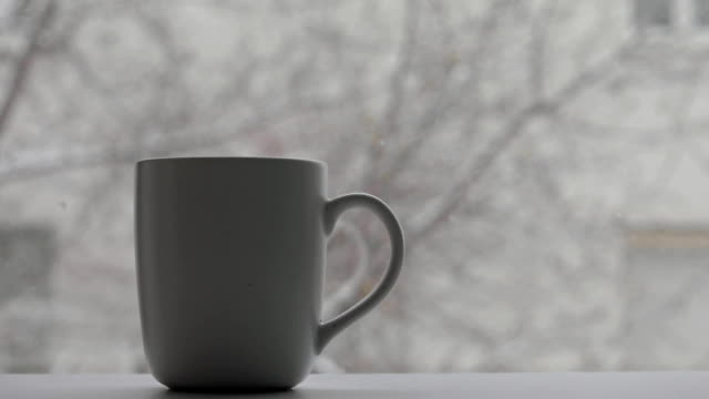 Cup with a hot drink and snow falls