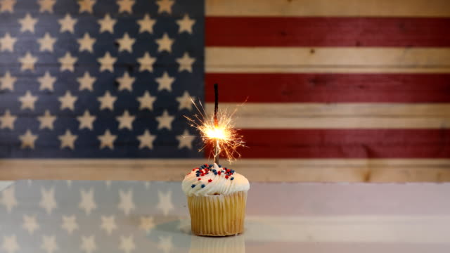 cupcake with sparkler for july 4th holiday - giorno dell'indipendenza video stock e b–roll