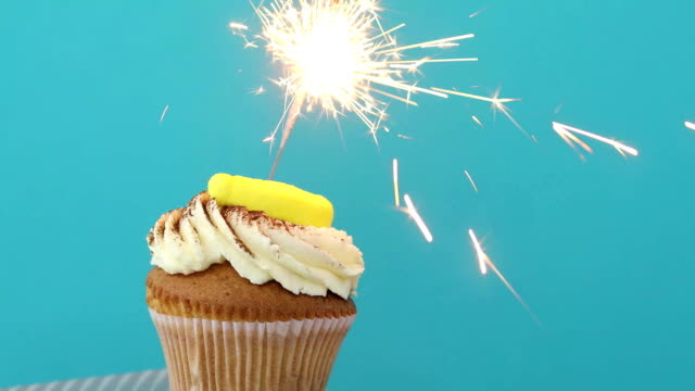 Cupcake with sprinkles and sparkler blue background Yellow Birthday cupcake with sprinkles and a sparkler over a blue background happy birthday stock videos & royalty-free footage