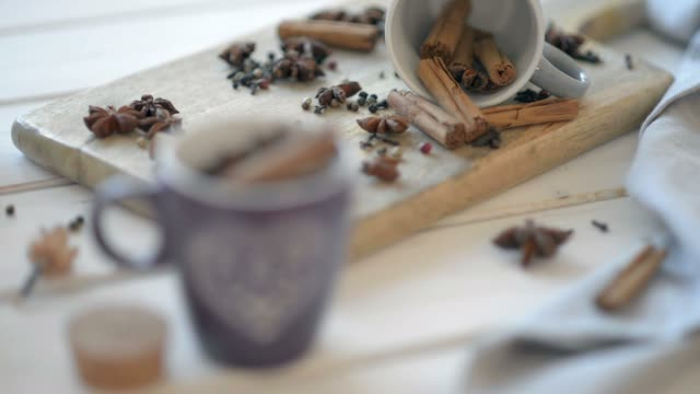 Cups with anise, cinnamon, cloves and pepper on a wooden old table. video