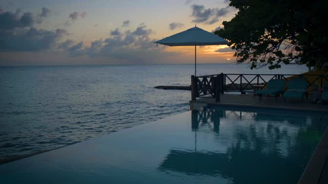 Curacao, couple on vacation in Curacao watching sunset by the pool Curacao, vacation in Curacao watching the sunset by the pool , sunset with beach chair and umbrella by pool curaçao stock videos & royalty-free footage