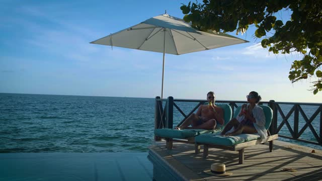 Curacao, couple on vacation in Curacao watching sunset by the pool Curacao, a couple on vacation in Curacao watching the sunset by the pool. mid age couple men and woman watching sunset over ocean curaçao stock videos & royalty-free footage