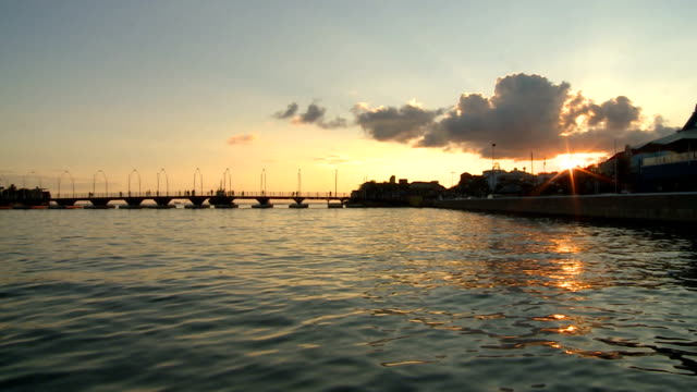 Curacao Harbor A wide shot of the seaside in the city of Curacao.  The sun is setting in the background as people traverse the bridge. curaçao stock videos & royalty-free footage