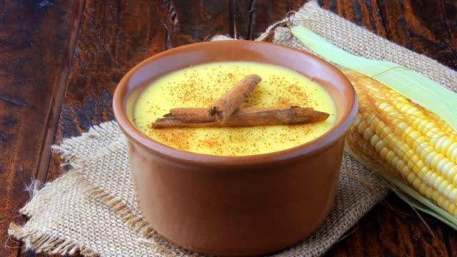 curau, mısır tatlısı krem ve tatlı brezilya mutfağının tipik, tarçın ahşap masa üzerine seramik kase yerleştirilir. - muhallebi stok videoları ve detay görüntü çekimi