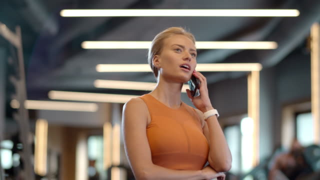 stockvideo's en b-roll-footage met nieuwsgierig atleetmeisje dat telefoon bij gymnastiek gebruikt. sportvrouw die zich in sportclub bevindt - call center