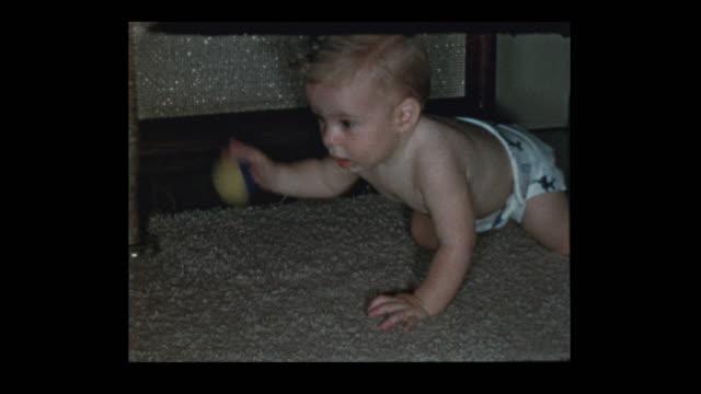 curious baby boy in diapers plays with ball - hotel reception filmów i materiałów b-roll