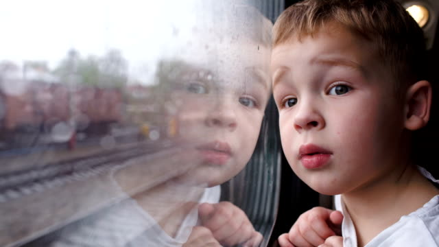 Curious boy looking out of the train window in rainy video