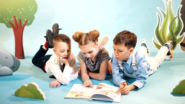 stockvideo's en b-roll-footage met nieuwsgierige kinderen lezen boek samen. - literatuur